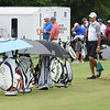 Golf bags are kept under cover with umbrella's on the driving range of The Greenbrier during The Greenbrier Classic Youth Day.<br /> (Rick BArbero/The Register-Herald)