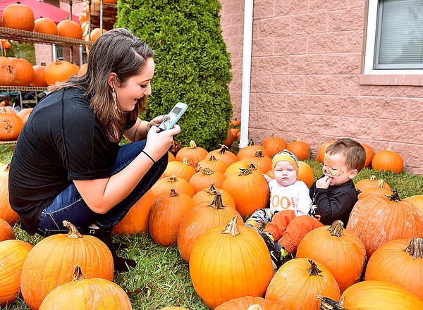 (Brad Davis/The Register-Herald) Beckley resident Jayci Petrey can't resist the opportunity for a photo of her two children Cannon Meadows (right), 2, and Hudson Petrey, 6 months, in a field of pumpkins during Burlington United Methodist Family Services' annual Pumpkin Festival Sunday afternoon near Prosperity.