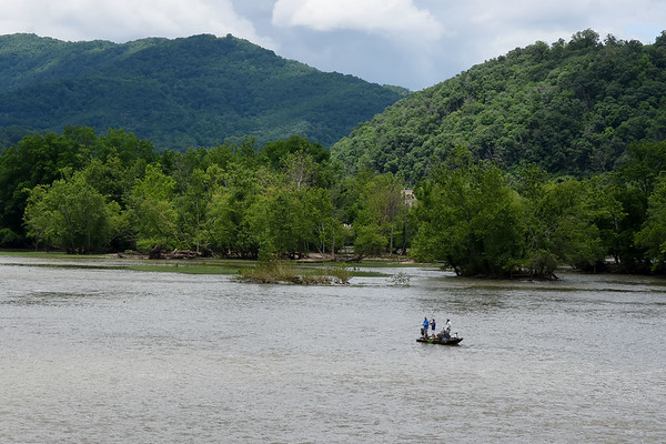 Three fishermen cast into the New River on their bass boat Wednesday near Hinton. (Chris Jackson/The Register-Herald)
