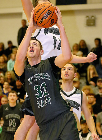 (Brad Davis/The Register-Herald) Wyoming East's Dylan Brehm drives to the basket as Westside defender Elijah Puett (background leaping) converges on him during the Warriors' win over the county rival Renegades Friday night in Clear Fork.