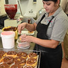 Sargat Dahal Thapa, putting sprinkles on donuts at the Donut Connection<br /> (Rick Barbero/The Register-Herald