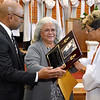 (Brad Davis/The Register-Herald) Brenda Clements (middle), widow of the late Beckley firefighter Charles Clements, holds back tears as she's presented with a special plaque by choir member Doris McCormick, right, honoring her late husband Charles Clements during Central Baptist Church's Black History Month celebration Sunday afternoon. Clements was the first African Amercian firefighter in Beckley and served over 20 years. He passed away in late January. Their son Charles Jr. helps to comfort his mother at left.