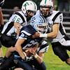 Fayetteville's Jordan Dempsey (9), Skyler Neal (66) and Kristopher Wilson (6) tackle Meadow Bridge's Nicholas White (23) during the first quarter of their football game Friday in Meadow Bridge. (Chris Jackson/The Register-Herald)