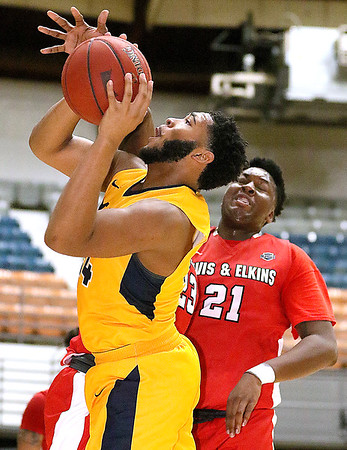 (Brad Davis/The Register-Herald) WVU Tech's Tamon Scruggs drives to the basket as Davis & Elkins' Rickenjee Bellevue (middle, hidden) and Trevor English, right, defend Saturday afternoon at the Beckley-Raleigh County Convention Center.