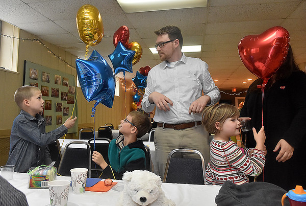 (Brad Davis/The Register-Herald) It's balloons and festivities for all as (from left) 8-year-olds Ben Terry, Jackson McClain and 6-year-old Evie Hilton finish up their snacks and desserts during St. Stephens Episcopal Church Day School's 60th anniversary celebration Sunday afternoon. Douglas Terry stands at middle.