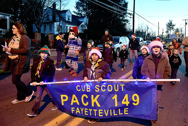 (Brad Davis/The Register-Herald) Young cub scouts from Troop 149 sing Christmas songs as they march along during Fayetteville's annual Christmas Parade Friday night.
