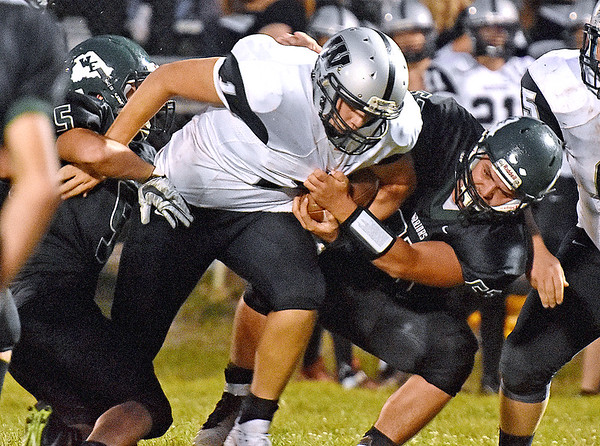 (Brad Davis/The Register-Herald) Westside quarterback Travis Cook is taken down by Wyoming East defenders Joseph Watson, left, and Christian Weis Friday night in New Richmond.