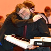 "(Brad Davis/The Register-Herald) Woodrow Wilson band director Bill Bailey looks gets a hug from Mary Sue Bailey, band director at Independence Middle School, as he's honored for over 45 years of teaching music during the intermission of Saturday's Southern West Virginia Honor Band performance, where he composed the Gold Band's performance. Bailey, president of the Raleigh County Bandmasters Association, is retiring later this year so Mary Sue Bailey and Liberty High School band director Jeremy Rodriguez presented him with a special plaque with a Hans Christian Andersen quote which reads ""When words fail, music speaks."""