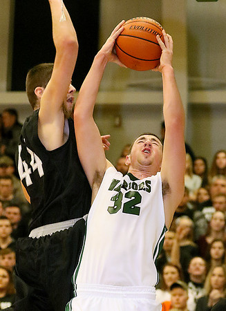 (Brad Davis/The Register-Herald) Wyoming East's Dylan Brehm drives to the basket as Westside's Corey Hatfield defends during the second boys meeting of the year in the battle for Wyoming County Friday night in New Richmond.