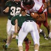 A Fayetteville defender gets a hit on Oak Hill's Christian Lively. Chad Foreman for the Register-Herald.