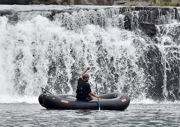(Brad Davis/The Register-Herald) A rafter cheers on his buddies as they conquer the falls in a variety of crafts, shortly before taking his own turn during Kanawaha Falls Fest Thursday morning in Gauley Bridge. The event was sponsored by ACE Adventure Gear and featured a whitewater kayak race, freestyle kayaking and even a photography contest open to spectators.