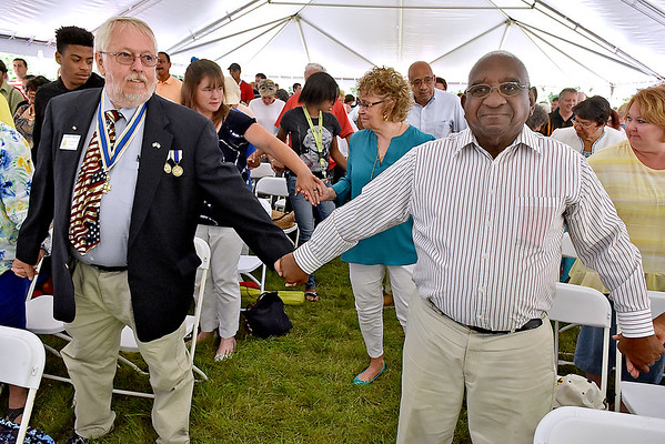 (Brad Davis/The Register-Herald) A massive, non-denominational congregation of White Sulphur Springs residents and many other surrounding community members all hold hands with one another as Rev. Kathy Holland delivers the benediction at the conclusion of the town's Service of Life & Rebirth Sunday afternoon in the new Brad Paisley Park. Mayor Lloyd Haynes joins in at right.