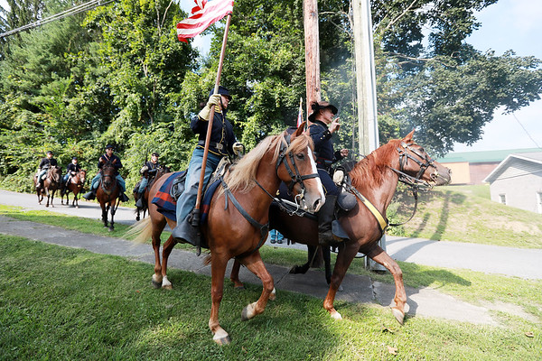 Civil War re-enactor's portraying the Federal Army cavalry race past the infantry after the local Home Guard on Pump St. during a battle between the local Home Guard and the Federal Army as part of Monroe County Heritage Day in Union on Saturday.  (Chris Jackson/The Register-Herald)