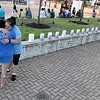 (Brad Davis/The Register-Herald) Cousins Mary Blevins and Lisa Figuerea share a hug as they reflect on the lives of family members lost to cancer as memorial luminaries are laid out during the American Cancer Society's Relay for Life atop Beckley's Intermodal Gateway Friday night.