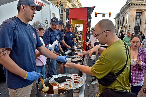 (Brad Davis/The Register-Herald) Beckley resident Josh Farley spends his last free hand to take an extra cup of chili from Beckley firefighter Ryan Arthur at BFD's booth during Beckley's annual Chili Night event Saturday evening.