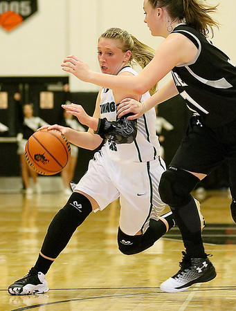 (Brad Davis/The Register-Herald) Wyoming East's Misa Quesenberry drives to the basket as Westside's Riana Kenneda defends Wednesday night in Clear Fork.