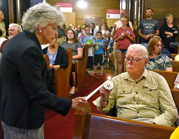 (Brad Davis/The Register-Herald) Mayor Andrea Pendleton assists congregants and town residents in  lighting their candles at the conclusion of Rainelle United Methodist's 2016 flood memorial service Friday night.