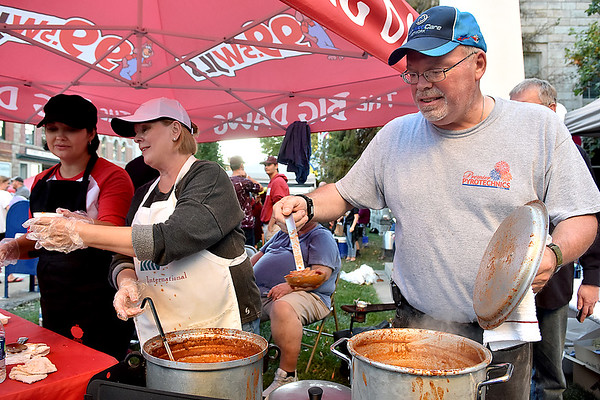 (Brad Davis/The Register-Herald) 99.5 WJLS Radio's Keith Thompson and Darlene Hodges (middle) keep hot chili cups coming during Beckley's annual Chili Night event Saturday evening.