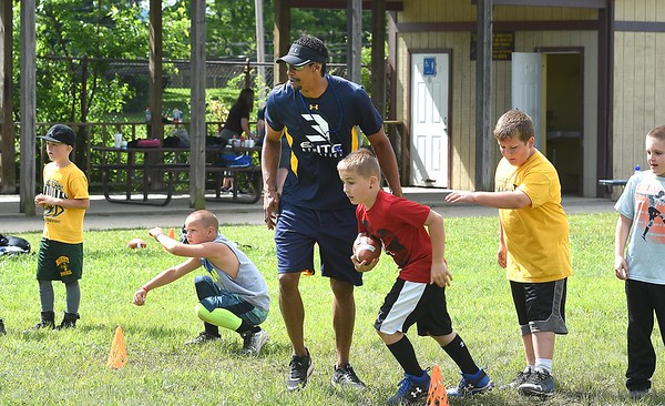 Ricky Sherrod, former WVU football player, third from left, works with youth during a youth football camp held in Coal City.<br /> (Rick Barbero/The Register-Herald)