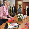 (Brad Davis/The Register-Herald) Attendee Kathryn Vance, Coordinator with Mountain State Combined Federal Campaign, begins cutting a special cake congratulating the United Way of Southern West Virginia during a ceremony announcing the organization has reached its yearly allocation goal of $855,000 Friday afternoon at their Croft Street headquarters.