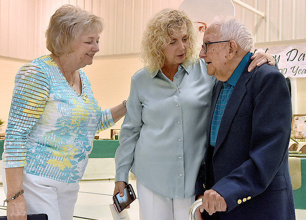 (Brad Davis/The Register-Herald) Harlan Mann, turning 100 years old next week, talks with two of his three daughters, Judy Lilly (left), his first, and Anita Walker, his youngest, during the opening moments of an early birthday party for him thrown by family at Beckley Regular Baptist Church Saturday evening.