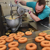 Jordan Southard making plain cake donuts at the Donut Connection.<br /> (Rick Barbero/The Register-Herald