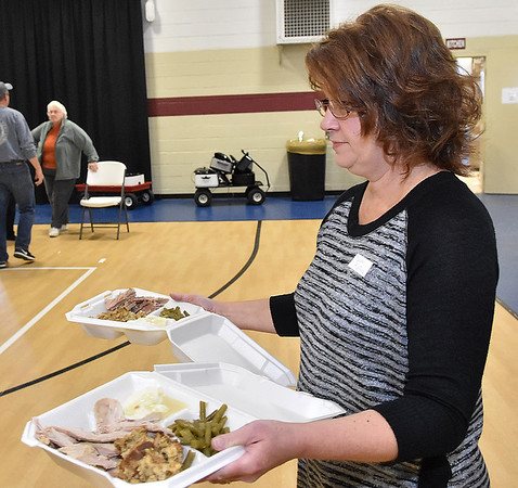 (Brad Davis/The Register-Herald) A volunteer carries out ready to order to-go plates during Lewis Christian Community Center's Thanksgiving dinner Thursday afternoon in Oak Hill.