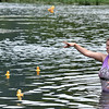 (Brad Davis/The Register-Herald) Race official Courtney Cox retrieves runaway duckies during this year's installment of the CFM House Museum's Great Rubber Ducky Race Sunday afternoon underneath the Veterans Bridge.