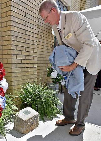 (Brad Davis/The Register-Herald) Tom Sopher unviels the 1932 marker that was discovered by contruction workers who were building new sidewalks and other concrete work around the Soldiers and Sailors Memorial in Beckley following a rededication ceremony Saturday afternoon. The marker once sat at the base of an American Elm Tree planted in honor of the nation's founding that was situated in a former green space that was where all the new concrete along McCreery street is.