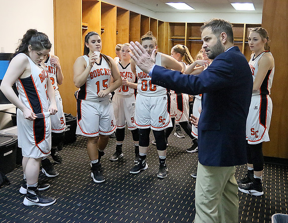(Brad Davis/The Register-Herald) Summers County players make final preparations as assistant coach Chad Meador, right, and head coach Sarah Blevins (unphotographed at left) review the game plan in the locker room following warmups prior to the Lady Bobcats' opening round State Tournament game against Charleston Catholic Wednesday evening at the Charleston Civic Center.