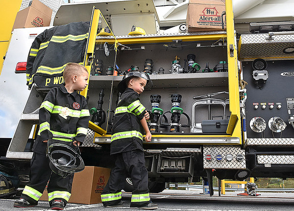 (Brad Davis/The Register-Herald) Aspiring young firefighters Elijsha Kinley (left), 3, and older brother Jesse, 5, check out all the cool gear inside Beaver Volunteer Fire Department's Ladder Tower 1 during a Raleigh County Firefighter Day event geared towards a mixture of showcasing firefighter tactics and attracting needed volunteers to several departments around the county.