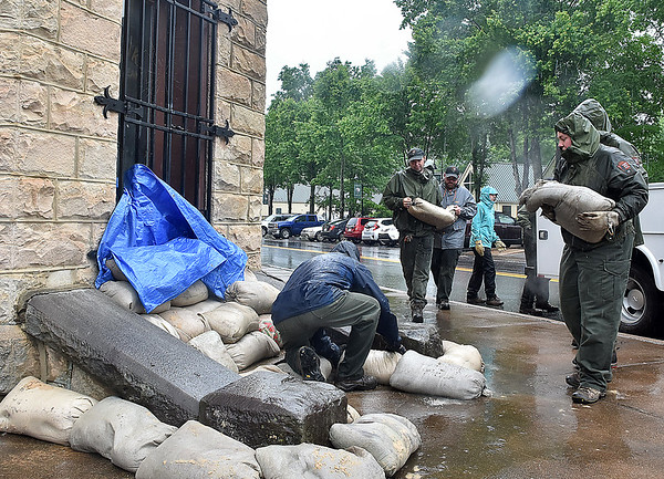 (Brad Davis/The Register-Herald) National Park Service personnel scramble to get sandbag barriers up around the old bank in Glen Jean as flood waters persist after heavy rains Monday afternoon.
