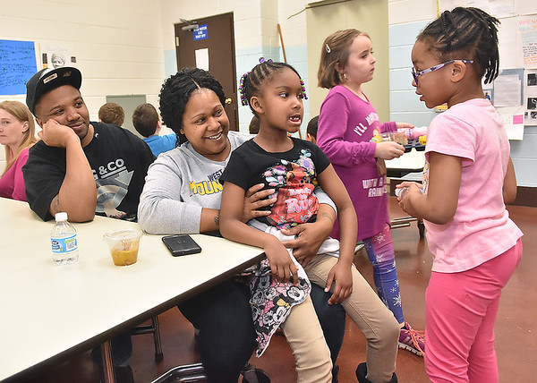 (Brad Davis/The Register-Herald) First grade classmates Myava Watson (far right), 6, and Sereniti Mickey (middle), 7, chat as Mickey's parents Stephanie and Brandon spend some time at a special Soul Food Luncheon Friday morning at Stratton Elementary School. Parents and guardians were invited to visit and sit down for a hot meal and some quality time with their hard-working kids and to check out all the students' special Black History Month projects, which hung on display through the cafeteria.