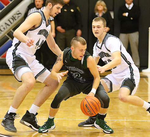 (Brad Davis/The Register-Herald) Wyoming East's Jon Sims tries to shake a double team from Westside defenders Cory Hatfield, left, and Jacob Ellis during the Warriors' win over the county rival Renegades Friday night in Clear Fork.