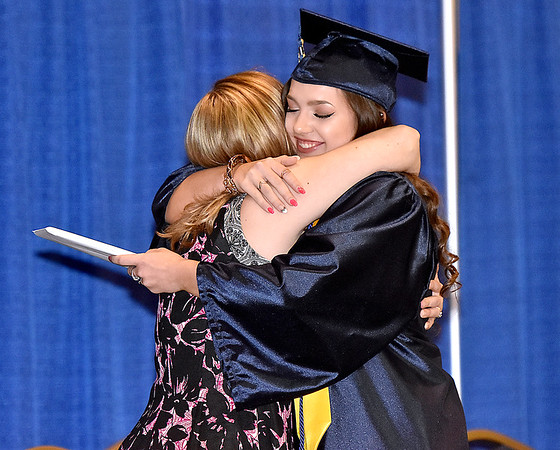 (Brad Davis/The Register-Herald) A graduating Nicholas County High School senior hugs teacher Samantha Murphy after collecting her diploma during the school's 103rd Commencement Ceremony Sunday afternoon at the Summersville Arena