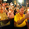 (Brad Davis/The Register-Herald) Congregants and town residents sing with their candles alight at the conclusion of Rainelle United Methodist's 2016 flood memorial service Friday night.