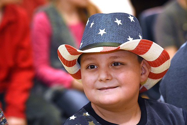 """Aaron Spence, second grader, listens to the first grade class sing, """"My Country Tis of Thee"""" during a Vereran's Day program held at Lester Elementary School Wednesday afternoon.<br /> (Rick Barbero/The Register-Herald"""