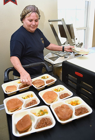 Cheryl Persinger packaging up lunches at the Greenbrier County Committee on Aging in Rupert.<br /> (Rick Barbero/The Register-Herald)