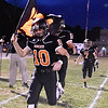 (Brad Davis/The Register-Herald) Summers County's Timmy Persiani carries the flag as he leads his teammates onto the field Friday night in Hinton.