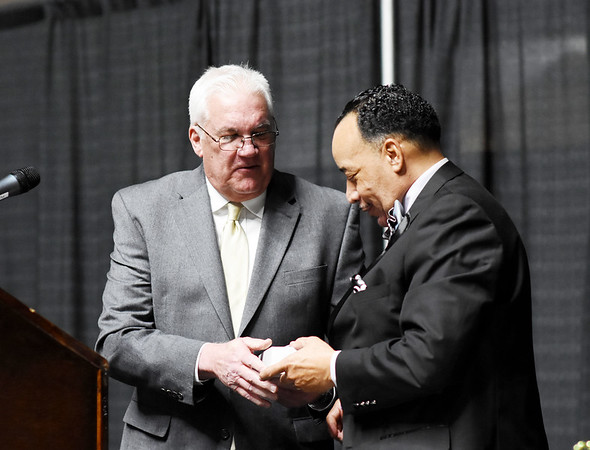 Beckley Mayor Rob Rappold hands Bishop Fred T. Simms the Key to the City of Beckley during the 31st annual Spirit of Beckley Award at the Beckley-Raleigh County Convention Center in Beckley on Monday. (Chris Jackson/The Register-Herald)