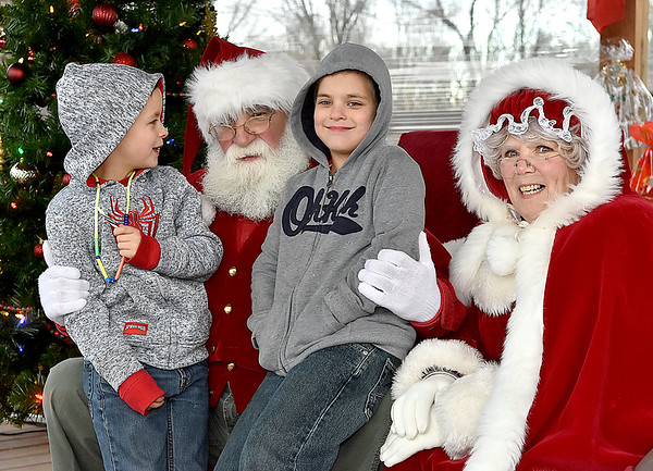 """(Brad Davis/The Register-Herald) Twin bothers Lucas, left, and Lennox Accord, 6, convey their Christmas wishes to Santa and Mrs. Claus during the 4th annual """" Santa at the Lighthouse"""" event Saturday evening on the grounds of the Summersville Lake Retreat. This year the sponsored school was Zela Elementary, where students in grades K-2nd were invited to meet Santa and Mrs. Claus, have some hot chocolate and receive bundles of gifts they otherwise wouldn't be able to enjoy."""