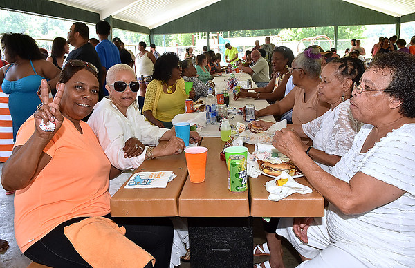 (Brad Davis/The Register-Herald) Beckley resident Evelyn Richardson, far left, notices the camera and gestures as she, Alzonia Smith (2nd from left), Valerie Long (far right), Willia Barnhart (2nd from right) and many other Beckley residents enjoy the day together at the 13th Annual Juneteenth Family Cookout Sunday afternoon at New River Park.