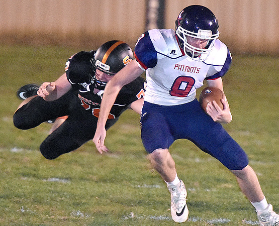(Brad Davis/The Register-Herald) Independence quarterback Adam Daniels eludes Summers County defender Ethan Koenig as he's forced to run Friday night in Hinton.