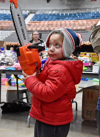 (Brad Davis/The Register-Herald) Three-year-old Tyler Butler chooses the chainsaw during the annual Mac's Toy Fund event Saturday morning at the Beckley-Raleigh County Convention Center.
