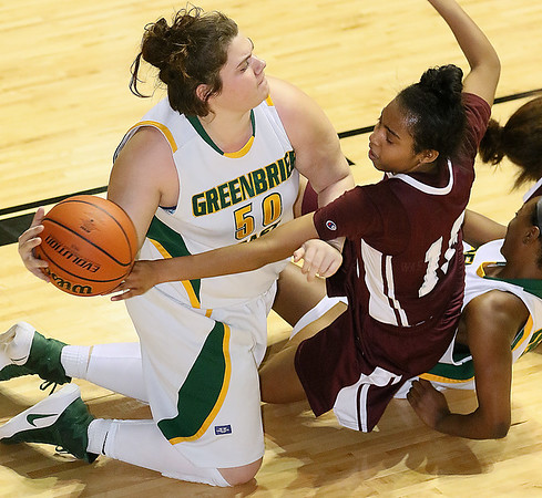 (Brad Davis/The Register-Herald) Greenbrier East's Piper Nunley wins the battle for a loose ball as Woodrow Wilson's Lyric Moon reaches for it during Big Atlantic Classic action Thursday night at the Beckley-Raleigh County Convention Center.