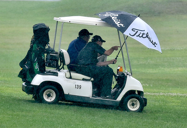 (Brad Davis/The Register-Herald) A pair of golfers use their umbrella to try and shield their faces from the stinging rain as they search for a ball during BNI action Saturday afternoon at Grandview Country Club.
