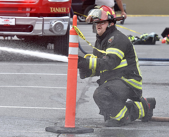 (Brad Davis/The Register-Herald) Bradley Volunteer Firefighter James Mullins deploys, assembles and uses a fire hose as quickly as possible during the obstacle course portion of a Raleigh County Firefighter Day event geared towards a mixture of showcasing firefighter tactics and attracting needed volunteers to several departments around the county Sunday afternoon at the Crossroads Mall.