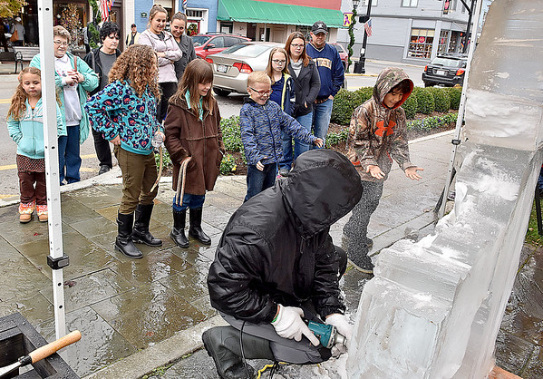(Brad Davis/The Register-Herald) Drawn in by the flying snow local youngsters gather around to watch and play in the spray as ice sculptor Steven Halliday crafts frozen blocks into a masterpiece during the Lewisburg Holiday Festival Saturday afternoon.