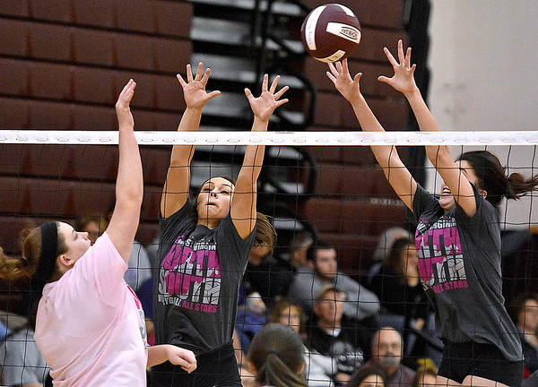 (Brad Davis/The Register-Herald) Greenbrier East's Maddie Cochran (middle) and a Class AAA (grey) teammate rush in to try and block an incoming spike from a squad of Class AA (pink) All-Stars during the West Virginia North/South All-Star Volleyball event Saturday afternoon at Woodrow Wilson High School.