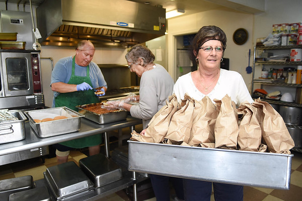 Lisa Gutshall carry lunches lunches to the truck at the Greenbrier County Committee on Aging in Rupert.